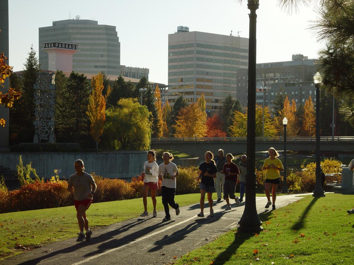 Runners along an urban trail surrounded by trees and the cityscape.
